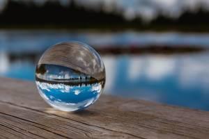 Himmel und See spiegeln sich in einer Glaskugel