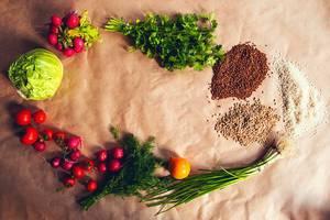 Hintergrund mit Lebensmitteln für eine gesunde Ernährung, mit frischem Gemüse und Getreide wie Radieschen, Lauchzwiebeln, Dill und Salat