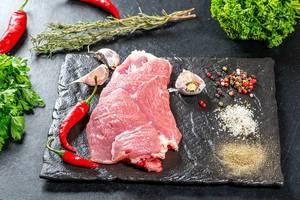 Hintergrundbild mit Zutaten zum Kochen: rohes Fleisch, Chilischoten, Knoblauchzehen, Kräuter und farbenfrohe Gewürze