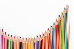 Hintergrundbild Schule: viele Buntstifte in einer Reihe, auf weißer Oberfläche