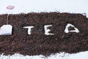"""Hintergrundbild zum Thema Tee: Das Wort """"Tea"""" in getrocknetem Tee, neben einem Teebeutel auf einem weißem Tisch"""