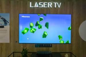 Hisense Sonic Laser TV 100L5 vor einer Holzwand, auf der IFA-Austellung in Berlin