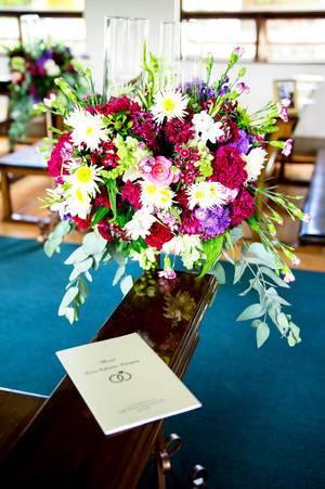 Hochzeits-Blumenstrauß mit dem Hochzeitsprogramm auf einer Bank in der Kirche