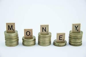 Hölzerne Buchstaben bilden das Wort MONEY auf Türmen aus Münzen