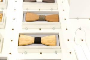 Hölzerne Fliegen für Herrenanzüge in Boxen auf weißem Verkaufsregal