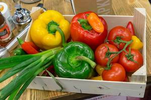 Hölzerne Kiste gefüllt mit Gemüse wie Paprika, Tomaten, Lauch und Chilis auf Holztisch