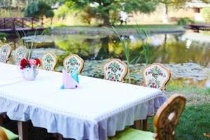 Hölzernem Tisch und Stühle vor einer Feier am See
