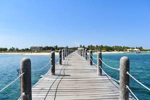 Hölzerner Steg führt über das Wasser zum mit Palmen gesäumten Strand