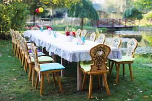 Hölzerner Tisch und Stühle für Outdoor-Party zum Kindergeburtstag vorbereitet