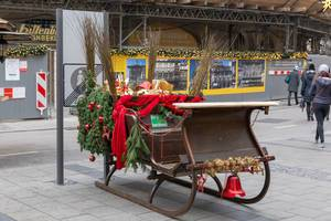 Hölzerner Weihnachtsschlitten, dekoriert mit Tannenzweigen, Geschenken und Nikolausruten