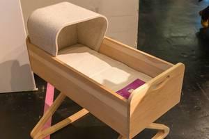 Hölzernes Babybett in Form einer Schublade mit Füßen in Form von Kleiderbügeln