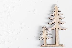 Holzfiguren eines großen und kleinen Weihnachstsbaums auf weißem Hintergrund mit mit Schnee Top view