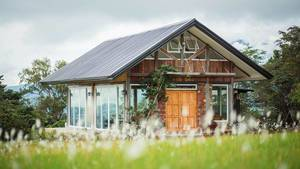 Holzhaus mit 360 Grad Blick auf grüne Umgebung durch umfassende Fensterfronten