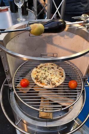 Holzkohlegrill mit Pizza und Gemüse