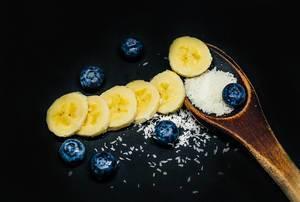 Holzlöffel mit Kokosraspeln, Bananenscheiben und Blaubeeren