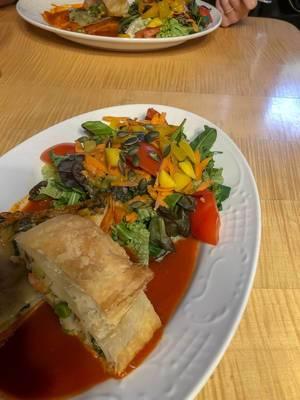 Holztisch mit zwei Tellern mit Gemüselasagne und grünem Salat in Tomatensoße