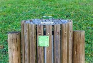 Holzverkleidete Mülltonne mit grünem Hinweisschild innerhalb eines Parks