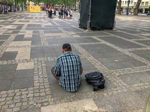 "Homeless man and drug addict at Neumarkt in front of visitors of the Cologne art festival ""Impulse Theater"" in Germany"