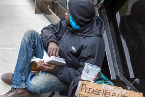 Homeless man sitting on the street, reading a book and begging for money