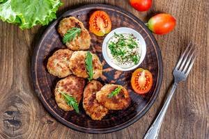 Homemade fried meat cutlets with sauce and herbs