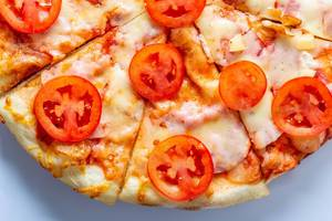 Homemade pizza with cheese and tomatoes