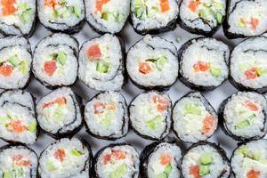 Homemade sliced Maki rolls with salmon, avocado and cucumber. Top view (Flip 2019)