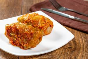 Homemade stuffed stewed in tomato sauce with knife and fork