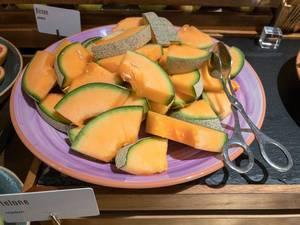 Honigmelonenstücke auf einem Teller zum bedienen mit einer Zange an einem Buffet