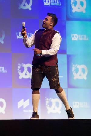 Host and speaker Dan Ram has fun on stage in his Oktoberfest outfit with lederhosen