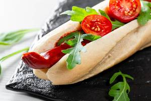 Hot dog with smoke sausage, arugula leaves, ketchup and tomatoes on a black stone tray