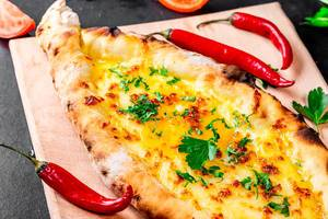 Hot open khachapuri with chicken egg and greens with chilli pepper