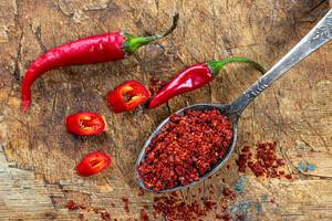 Hot red chili peppers and red pepper flakes in spoon on old wooden background