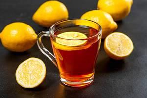 Hot tea with fresh yellow lemons on black background (Flip 2019)