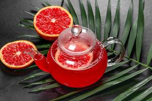 Hot tea with slices of fresh grapefruit on black background with green leaf (Flip 2019)