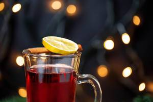 Hot wine with a sliced orange and cinnamon in the front and warm lights in the background