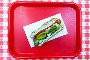 Hotdog nach Chicagoer Art: amerikanischer Senf, gehackte weiße Zwiebeln, Essiggurke, Tomatenscheiben und eingelegte Paprika