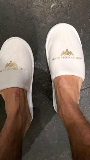 Hotelgast trägt weiße Hausschlappen vom Luxushotel Bayerischer Hof in München