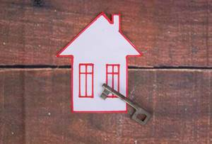 House with key on wooden background