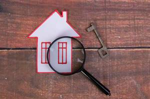House with magnifying glass on wooden background
