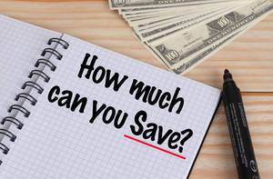 How much can you Save text in notebook and Dollar banknotes on wooden table