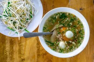 Hu Tieu Brühe mit Schweinefleisch, Wachtelei und Bohnensprossen auf Holztisch in Vietnam