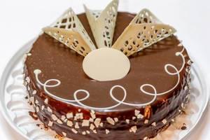 Hübsch dekorierter Geburtstagskuchen mit Schokoladenglasur auf weißer Kuchenschale