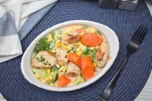 Hühnchen Kasserolle mit Karotten, Mais, Brokkoli und Erbsen in weißer Porzellanschale auf blauem Tischset mit Gabel