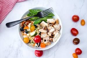 Hühnchenfleisch mit Gemüse-Salat und Zuckerschoten, in einer weißen Schale, aus der Sicht von oben