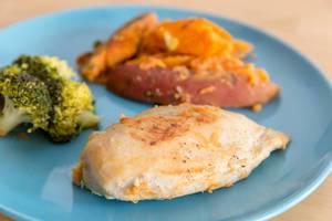Hühnerbrust mit Broccoli und Süßkartoffeln auf einem Teller in der Nahaufnahme  - Bokeh