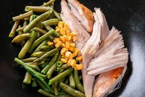 Hühnerfilet mit Spargel und Mais, auf einem schwarzen Teller in der Nahaufnahme
