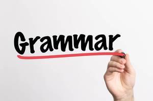 Human hand writing Grammar on whiteboard