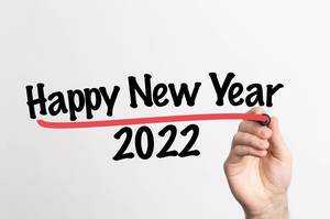 Human hand writing Happy New Year 2022 on whiteboard