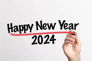 Human hand writing Happy New Year 2024 on whiteboard