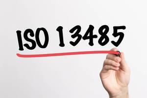 Human hand writing ISO 13485 on whiteboard